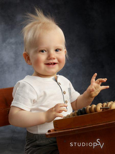 1-vuotiaalle mitoitettu pulpetti on säilyttänyt paikkansa Studio P.S.V:n lapsikuvauksissa jo melkein 20 vuotta. Siinä on vain niin kiva istua ja leikkiä - ja hupsista, samalla saadaan talteen hauskoja kuvia erilaisilla ilmeillä. Valokuvaaja Reijo Koirikivi.